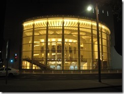 Habima Theater which has champaign glass style pillars lit up at night.