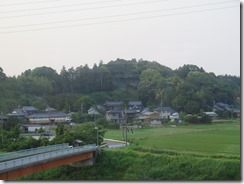 Houses and rice patties along the ride to Tokyo with forested hills in the background.
