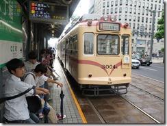 An older model tram at a station.